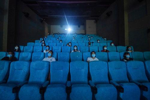 يتبع روّاد السينما في هانجتشو بالصين معايير جديدة للتباعد وارتداء الكمامات.